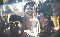Revellers at a summer music festival young bearded man wearing yellow sunglasses and women with feather headdress and painted faces. - MINF05568