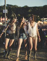 Three young women at a summer music festival wearing hot pants and Wellington boots, feather headdress and faces painted, arms around shoulder and smiling. - MINF05571