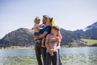 Austria, Tyrol, Walchsee, happy family at the lake - JLOF00153