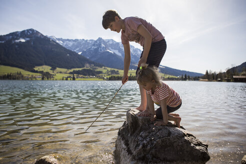 Austria, Tyrol, Walchsee, brother and sister playing in the lake - JLOF00156