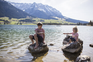 Austria, Tyrol, Walchsee, brother and sister sitting on boulders in the lake playing with sticks - JLOF00159