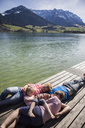 Austria, Tyrol, Walchsee, family lying on a jetty at the lakeside - JLOF00165
