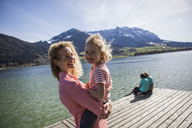 Austria, Tyrol, Walchsee, happy mother carrying daughter at the lake - JLOF00174