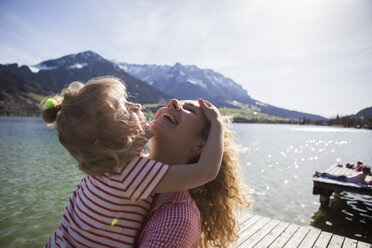 Austria, Tyrol, Walchsee, happy mother with daughter at the lake - JLOF00177