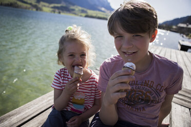 Austria, Tyrol, Walchsee, portrait of brother and sister sitting on jetty at a lake eating ice cream cones - JLOF00180