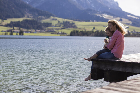 Austria, Tyrol, Walchsee, happy mother and daughter sitting on a jetty at the lake - JLOF00183
