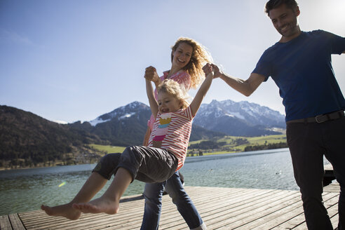Austria, Tyrol, Walchsee, happy parents swinging their daughter at the lake - JLOF00186