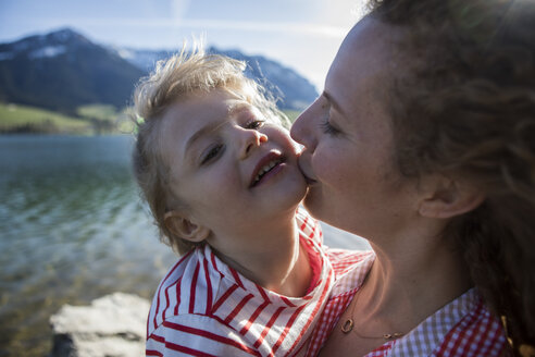 Austria, Tyrol, Walchsee, mother kissing happy daughter at the lake - JLOF00192