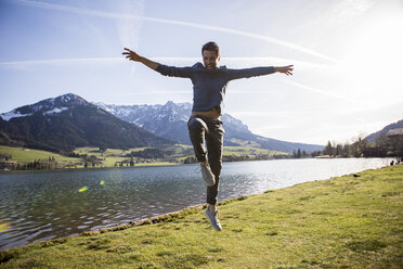 Austria, Tyrol, Walchsee, happy man jumping at the lake - JLOF00195