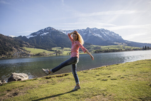 Austria, Tyrol, Walchsee, happy woman striding at the lake - JLOF00198