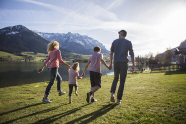 Austria, Tyrol, Walchsee, happy family walking at the lakeside - JLOF00201