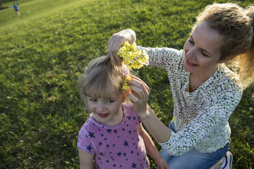 Austria, Tyrol, Walchsee, mother putting flowers into daughter's hair on an alpine meadow - JLOF00207