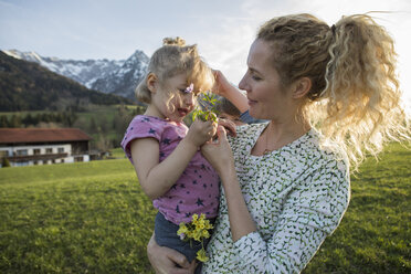 Austria, Tyrol, Walchsee, mother carrying daughter with flowers on an alpine meadow - JLOF00210