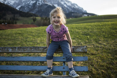 Austria, Tyrol, Walchsee, happy girl on a bench - JLOF00213