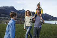 Austria, Tyrol, Walchsee, happy family hiking on an alpine meadow - JLOF00216