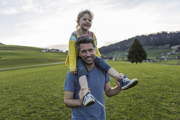 Austria, Tyrol, Walchsee, happy father carrying daughter piggyback on an alpine meadow - JLOF00219
