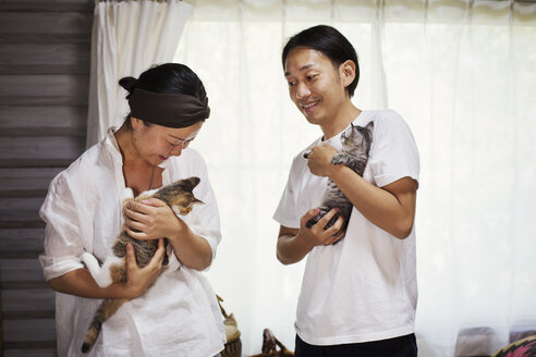 Man and woman standing indoors, each holding calico cat with white, black and brown fur. - MINF05949