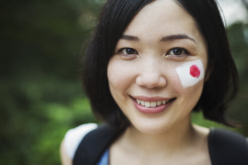 Portrait of young woman with black hair, Japanese flag painted on her cheek, smiling at camera. - MINF06003