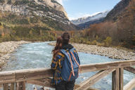 Spain, Ordesa y Monte Perdido National Park, back view of woman with backpack on wood bridge - AFVF01290