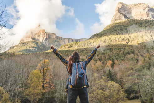 Spain, Ordesa y Monte Perdido National Park, back view of happy woman with backpack looking at view - AFVF01299