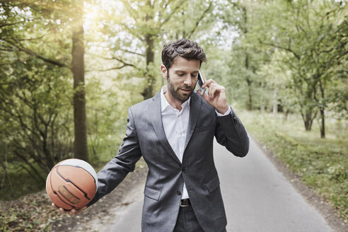 Businessman with basketball talking on smartphone on rural road - RORF01363