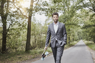 Businessman walking with skateboard on rural road - RORF01366