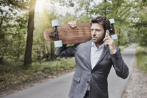 Businessman with skateboard talking on smartphone on rural road - RORF01369