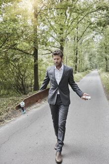 Businessman walking with skateboard and smartphone on rural road - RORF01372