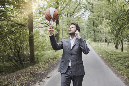 Businessman balancing basketball and talking on smartphone on rural road - RORF01375