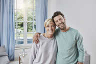 Portrait of happy couple embracing at home - RORF01378