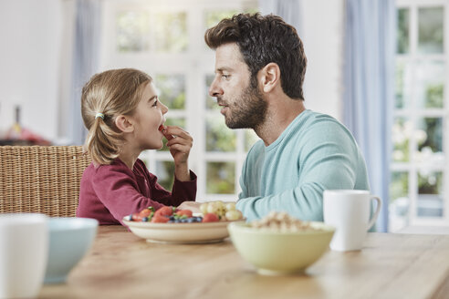 Father and daughter eating fruit at home - RORF01390