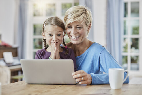 Mother and surprised daughter using laptop at home - RORF01393