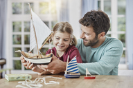 Happy father and daughter playing with model boat at home - RORF01396