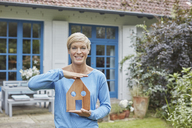 Portrait of smiling woman standing in front of her home holding house model - RORF01408