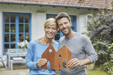 Portrait of smiling couple standing in front of their home holding house model - RORF01411