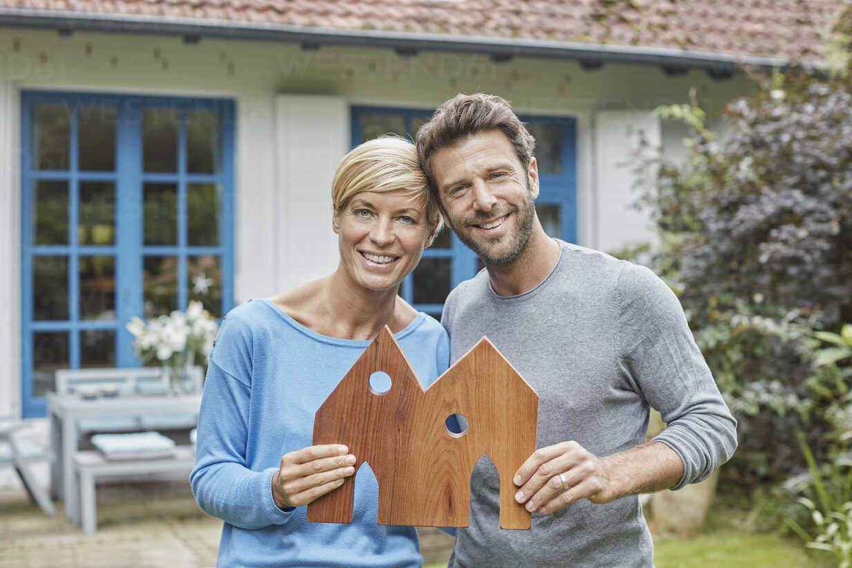 Portrait of smiling couple standing in front of their home holding house model - RORF01411 - Roger Richter/Westend61