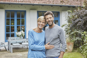 Portrait of smiling couple standing in front of their home - RORF01414