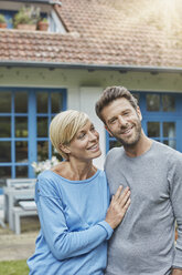 Portrait of smiling couple standing in front of their home - RORF01417