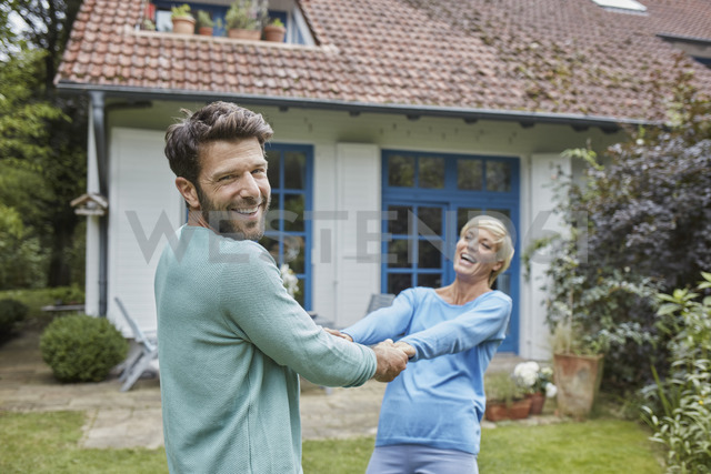 Happy couple dancing in front of their home - RORF01423 - Roger Richter/Westend61