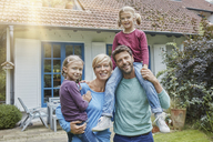 Portrait of happy family with two kids in front of their home - RORF01426