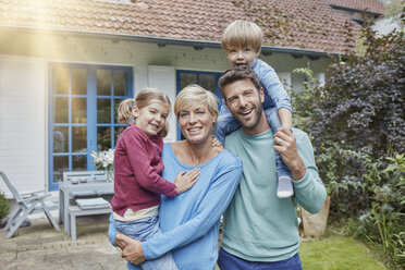 Portrait of happy family with two kids in front of their home - RORF01429