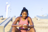 Young sportive woman using smartphone - AFVF01321