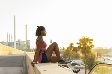 Young woman during workout sitting on wall at street - AFVF01327
