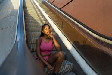 Young sportive woman sitting on escalator - AFVF01333