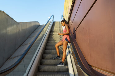 Young sportive woman on escalator using smartphone - AFVF01336
