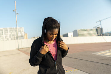 Young sportive woman listening music with headphones - AFVF01342