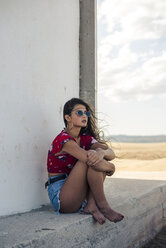 Portrait of teenage girl wearing sunglasses sitting among the shades looking at distance - ACPF00159