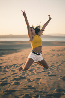 Happy teenage girl jumping in the air on the beach at sunset - ACPF00183