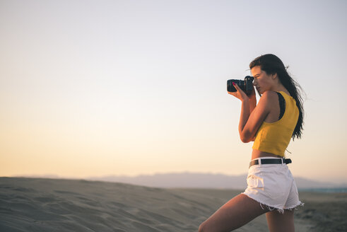 Teenage girl taking photos with camera on the beach at sunset - ACPF00186