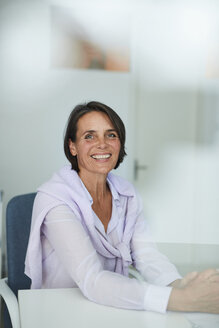 Portrait of mature businesswoman sitting at desk in an office - PNEF00843
